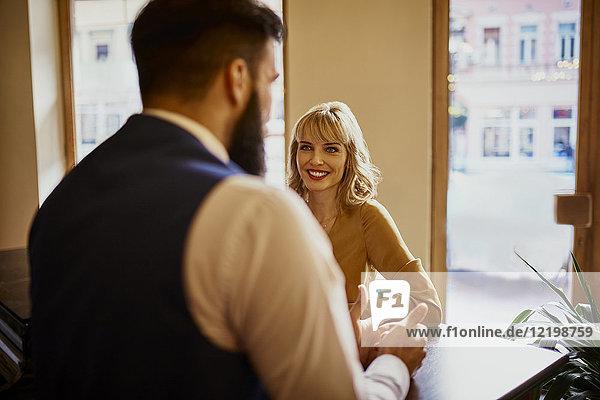 Elegante Frau lächelt den Mann in einer Bar an.