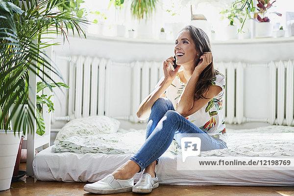 Fröhliche junge Frau  die zu Hause telefoniert.