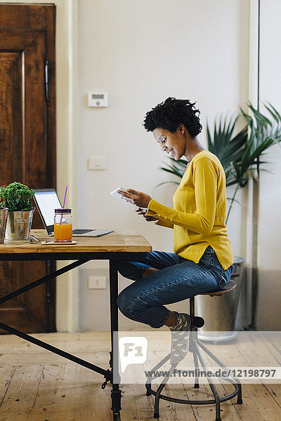 Young woman sitting at home reading on digital tablet