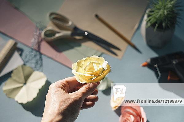Weibliche Hand mit Papierrose