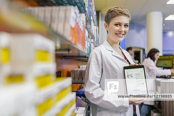 Porträt des lächelnden Apothekers in der Apotheke mit digitaler Bestellung