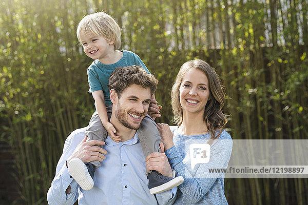 Porträt der glücklichen Familie im Garten vor Bambuspflanzen