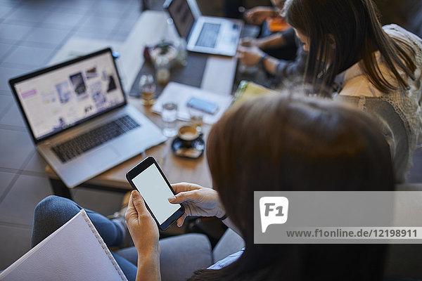 Junge Frau im Café mit Smartphone und Freunden mit Laptop im Hintergrund