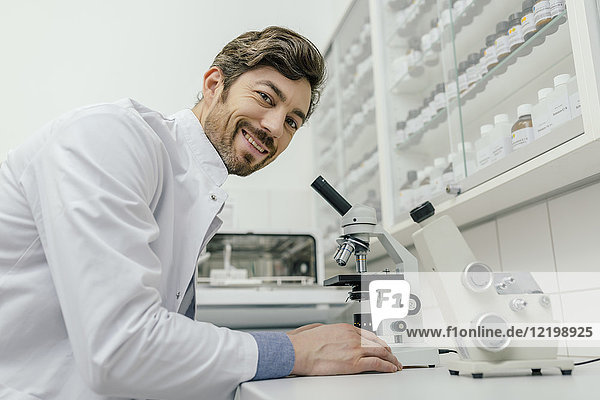 Porträt eines lächelnden Mannes unter dem Mikroskop im Labor