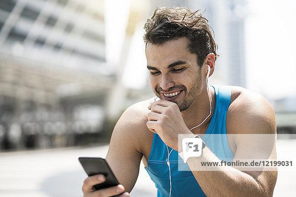 Läufer mit Kopfhörern  der Nachrichten auf seinem Smartphone abruft