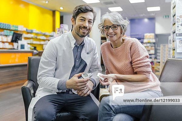 Portrait des lächelnden Apothekers und Kunden mit Blutzuckermessgerät in der Apotheke