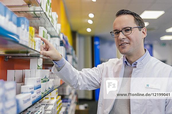 Porträt eines lächelnden Apothekers mit Medikamenten im Regal in der Apotheke