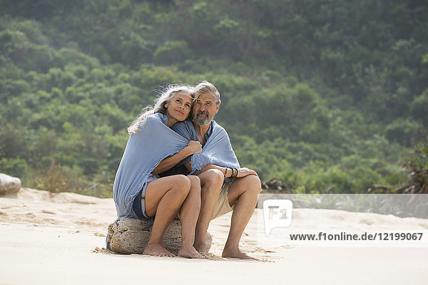 Seniorenpaar am Strand sitzend  in eine Decke gehüllt