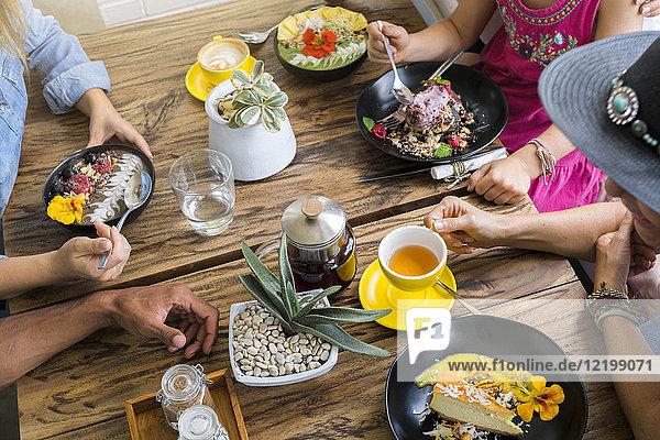 Menschen  die sich um einen Holztisch versammeln und verschiedene Speisen essen und trinken.