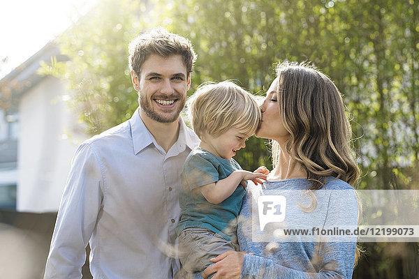 Glückliche Familie im Garten vor Bambuspflanzen mit Mutter küssendem Sohn