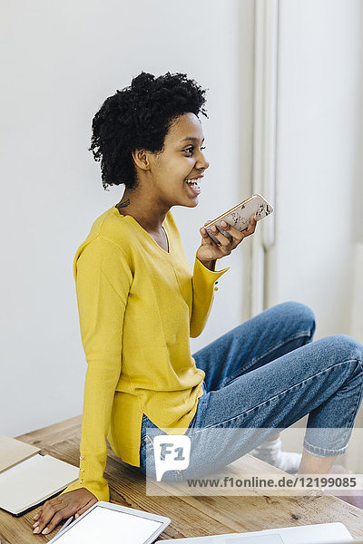 Young woman at home using smartphone