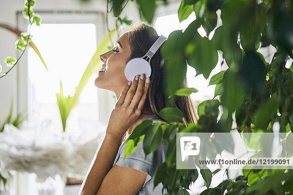 Lächelnde junge Frau mit Kopfhörer beim Musikhören in der Zimmerpflanze