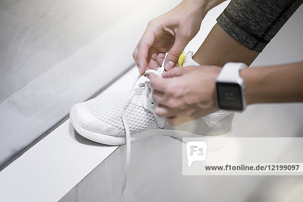 Close up of female hands tying sneakers with smartwatch