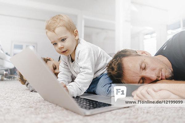 Eltern schlafen mit einem kleinen Mädchen und benutzen einen Laptop auf dem Boden.