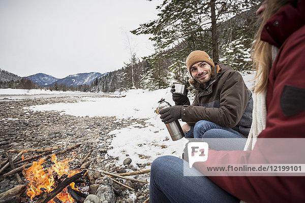 Paar auf einer Reise im Winter bei einem heißen Getränk am Lagerfeuer