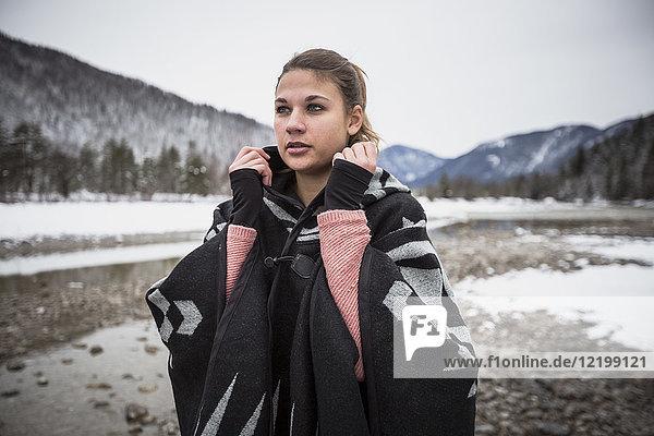 Junge Frau steht im Winter an einem Fluss
