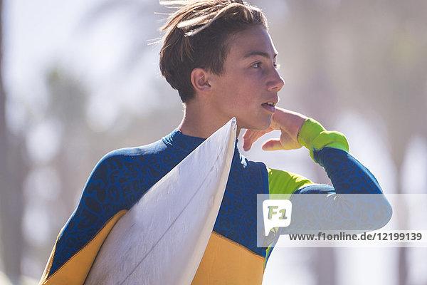 Portrait eines jungen Surfers mit Surfbrett