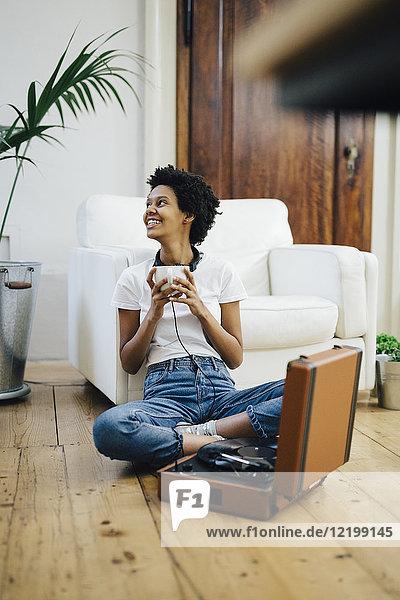 Junge Frau auf dem Boden sitzend  Musik vom Plattenspieler hörend  Kaffee trinkend