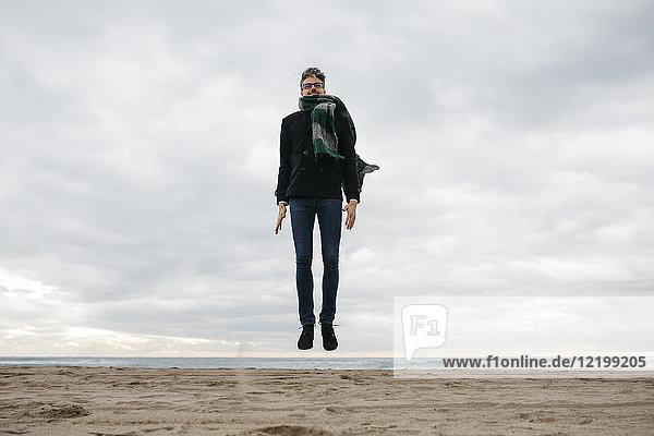 Mann beim Springen am Strand im Winter