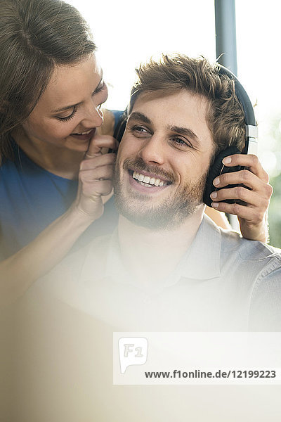Lächelnde Frau setzt Kopfhörer auf Freund auf
