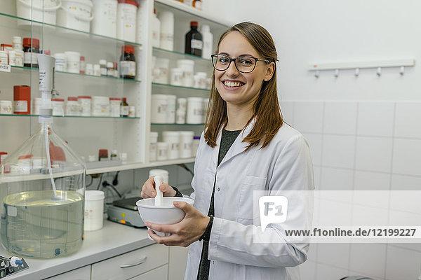 Porträt einer lächelnden Frau  die im Labor einer Apotheke eine Salbe herstellt.