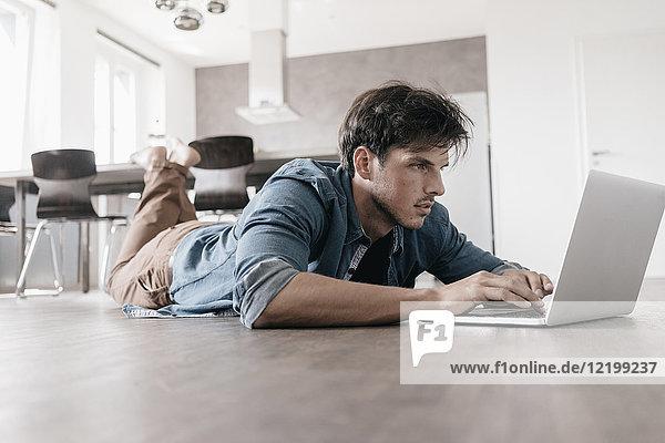 Mann auf dem Boden liegend in einem Loft mit Laptop
