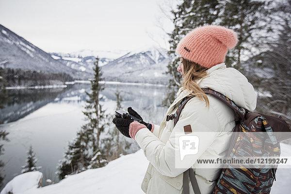 Junge Frau mit Handy in alpiner Winterlandschaft mit See