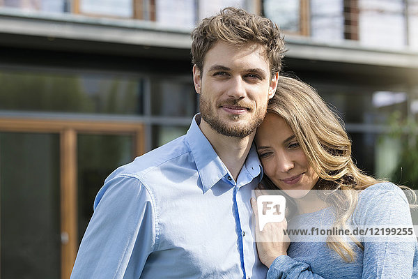 Porträt eines lächelnden  liebevollen Paares vor der Haustür