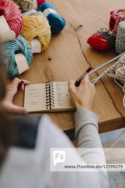 Nahaufnahme der Frau beim Notieren auf dem Tisch mit Stricken