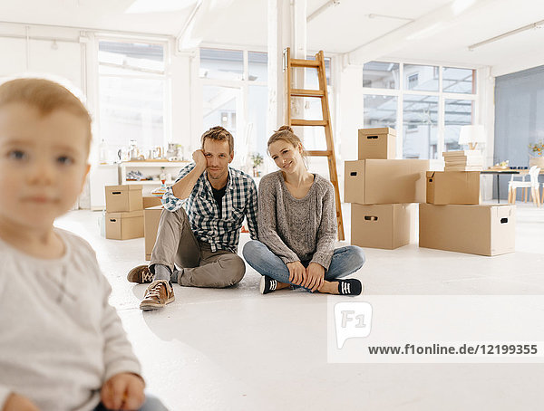 Lächelndes Paar mit kleiner Tochter zieht in ein neues Zuhause.