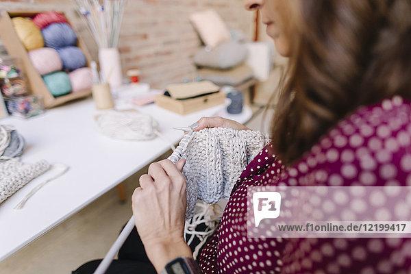 Close-up of woman knitting at table