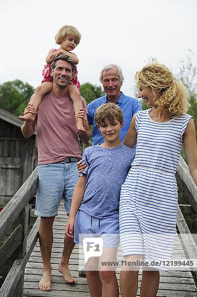 Glückliche Familie beim gemeinsamen Spaziergang auf der Strandpromenade im Sommer