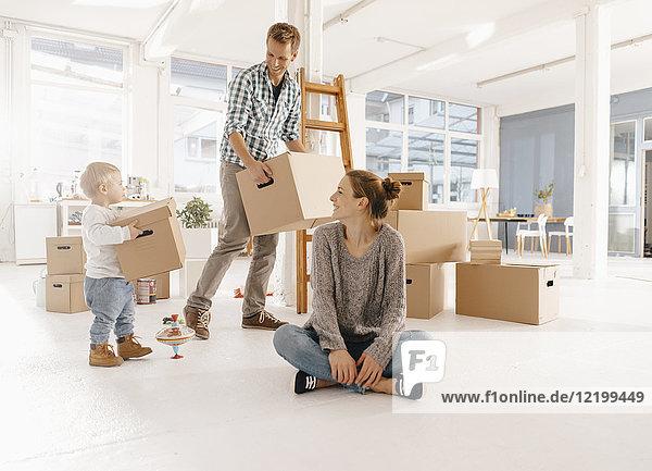 Glückliche Familie zieht in ein neues Zuhause mit Vater und Tochter  die Pappkartons tragen.