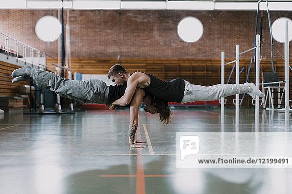 Zwei Männer bei der Akrobatik im Fitnessstudio
