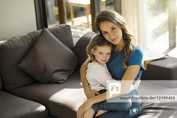 Porträt einer lächelnden Mutter  die ihre Tochter zu Hause auf dem Sofa hält.