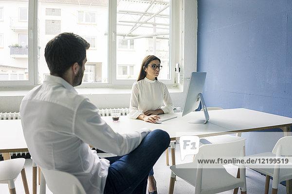 Mann sitzt der Frau gegenüber und benutzt den Computer im Büro.