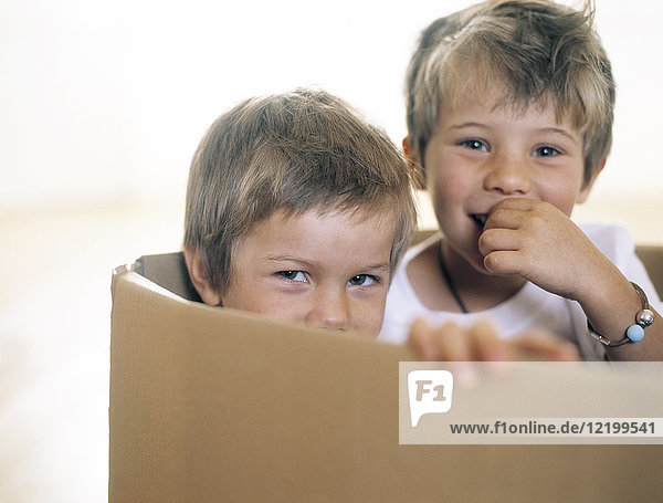 Two happy little children together in a cardboard box