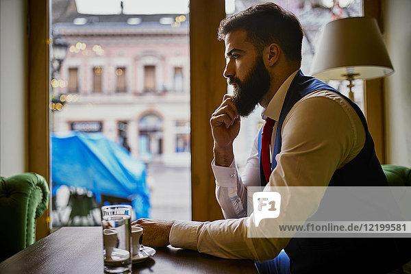 Nachdenklicher  modischer junger Mann sitzt in einem Café