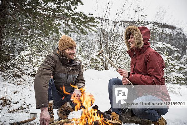 Glückliches Paar auf einer Reise im Winter bei einer Pause am Lagerfeuer