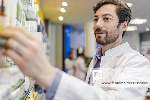 Apotheker  der Medikamente aus dem Regal in der Apotheke nimmt