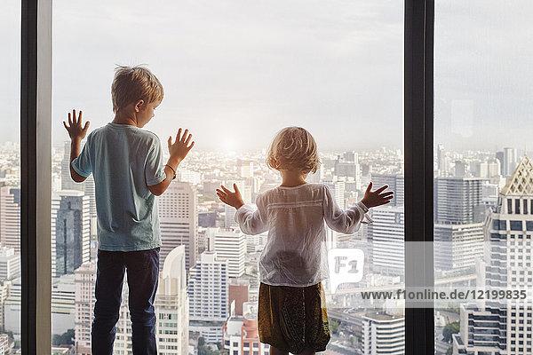 Thailand  Bangkok  Junge und kleines Mädchen schauen durchs Fenster ins Stadtbild