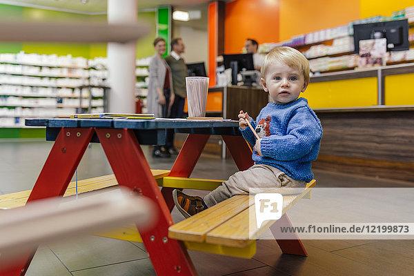 Kleiner Junge auf Bank in der Apotheke mit Eltern im Hintergrund