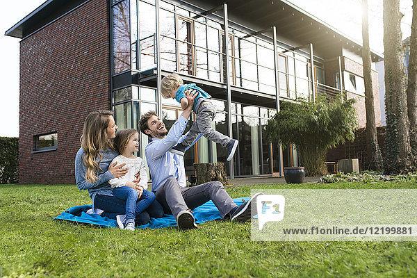 Glückliche Familie auf Decke im Garten vor ihrem Haus mit Vater  der den Sohn beleuchtet.
