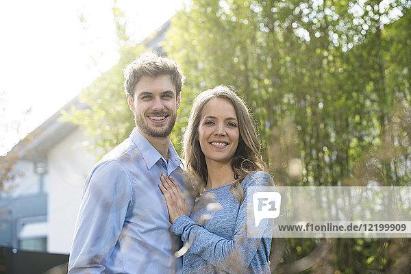 Porträt eines lächelnden Paares im Garten vor Bambuspflanzen