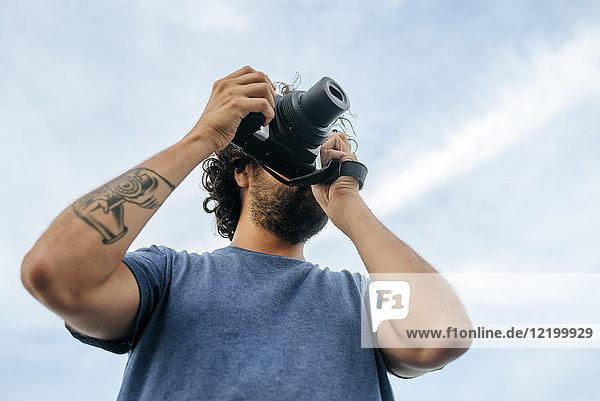 Panama  Bocas del Toro  Mann mit Kamera und Kameratattoo auf dem Arm