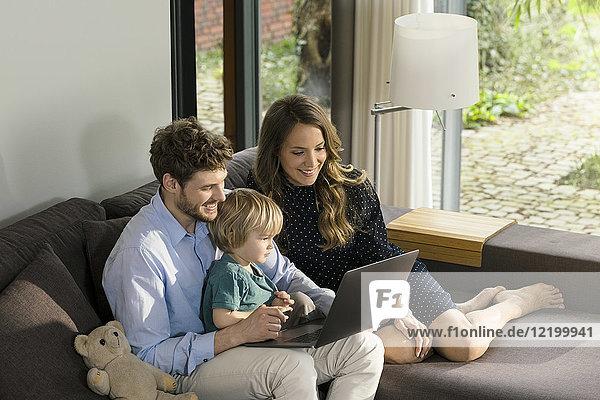 Lächelnde Eltern und Sohn sitzen auf dem Sofa und benutzen den Laptop zu Hause.