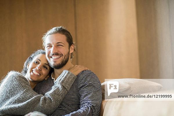 Porträt eines glücklichen jungen Paares  das auf der Couch sitzt.