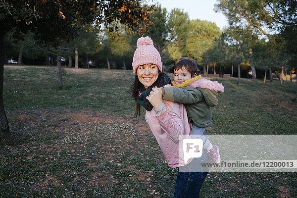 Glückliche Mutter trägt kleine Tochter Huckepack auf einer Wiese