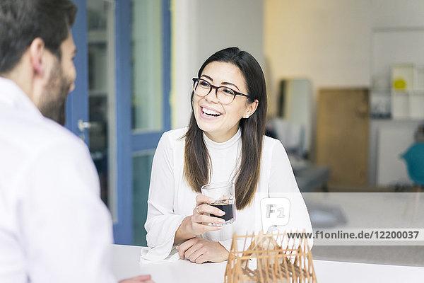 Frau lacht über Mann mit Architekturmodell auf Tisch