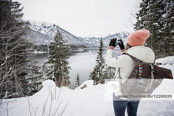 Junge Frau fotografiert in alpiner Winterlandschaft mit See